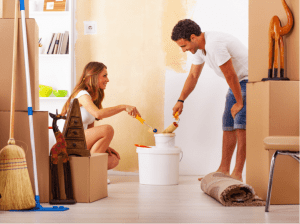 Couple painting a wall in home